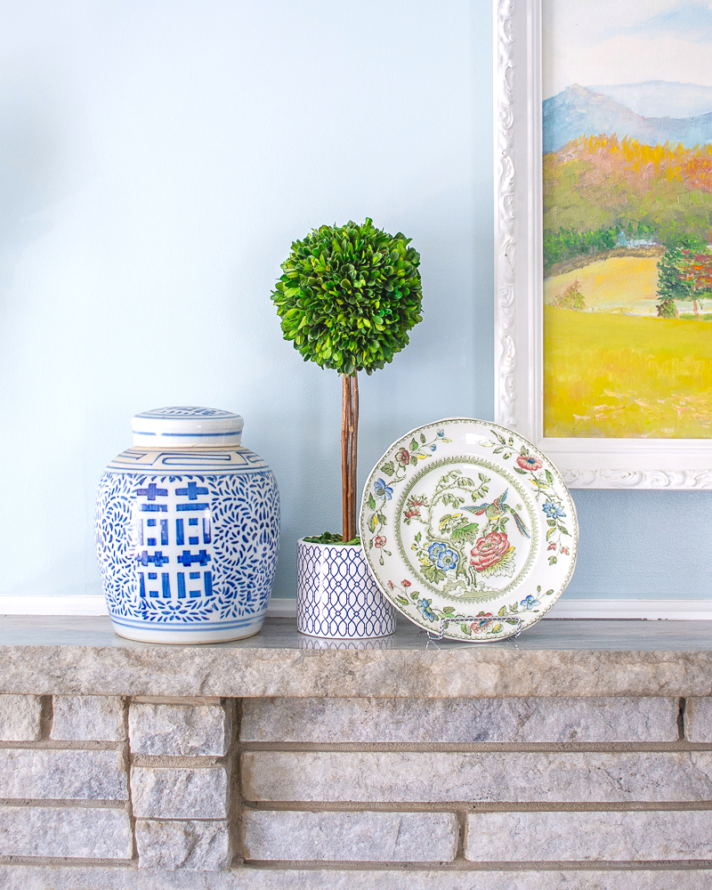Mantel decor with blue and white double happiness ginger jar, boxwood topiary, and bird of paradise plate