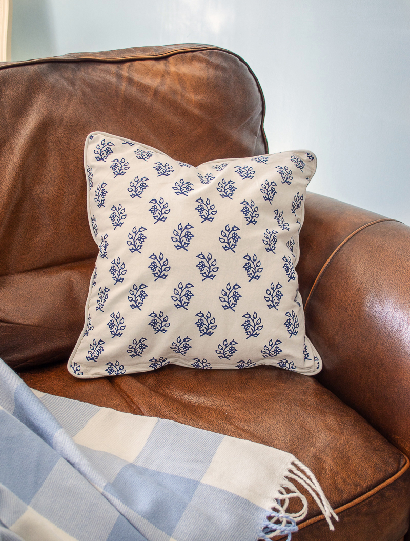 Blue and white Indian block print style pillow from Birch Lane brightens up this dark leather arm chair