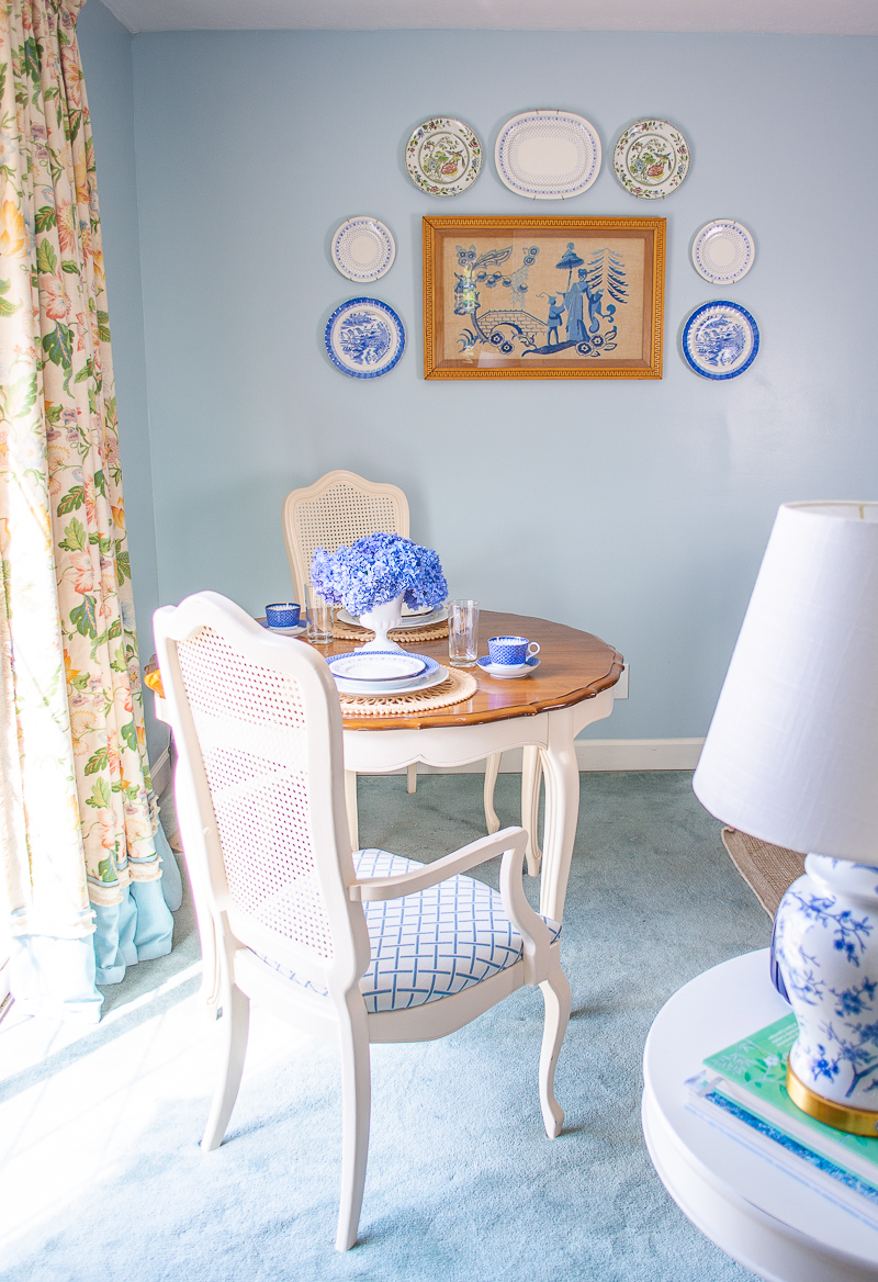 Side view of breakfast table in blue and white family room with white cane chairs, hydrangea centerpiece, and trellis fabric