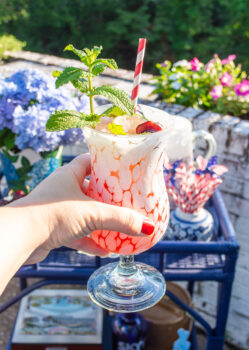 Cherry mint lemonade cocktail in white splatterware glass with paper straw and mint sprig