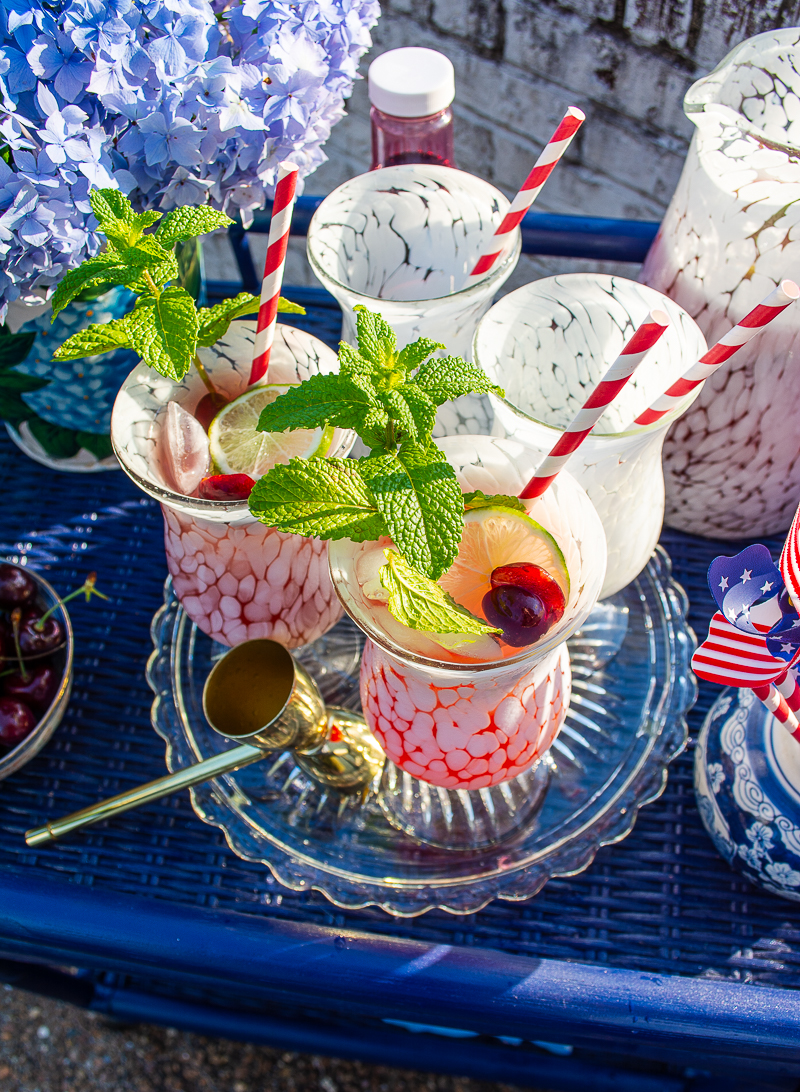 Glasses being filled with cherry mint lemonade for a 4th of July party