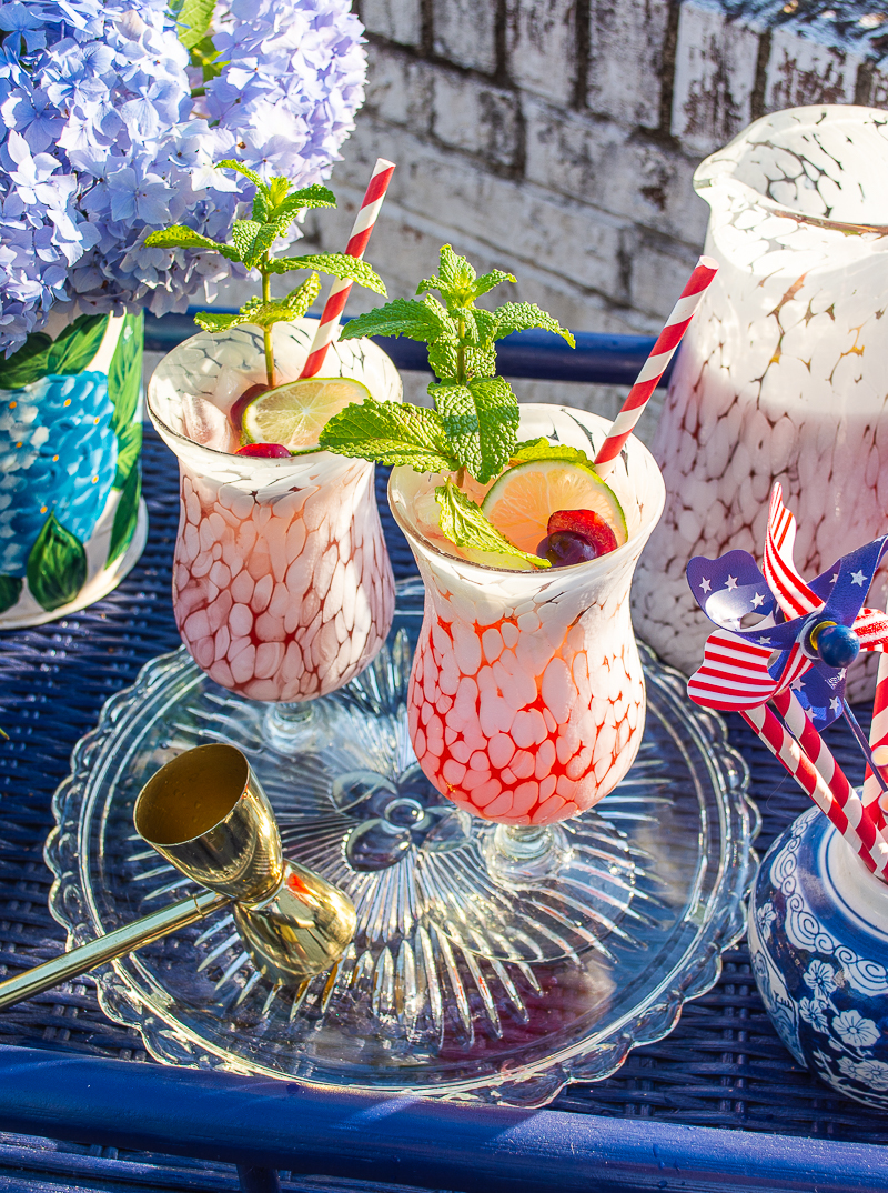 Cherry mint lemonade cocktails on navy bar cart decorated for the 4th of July