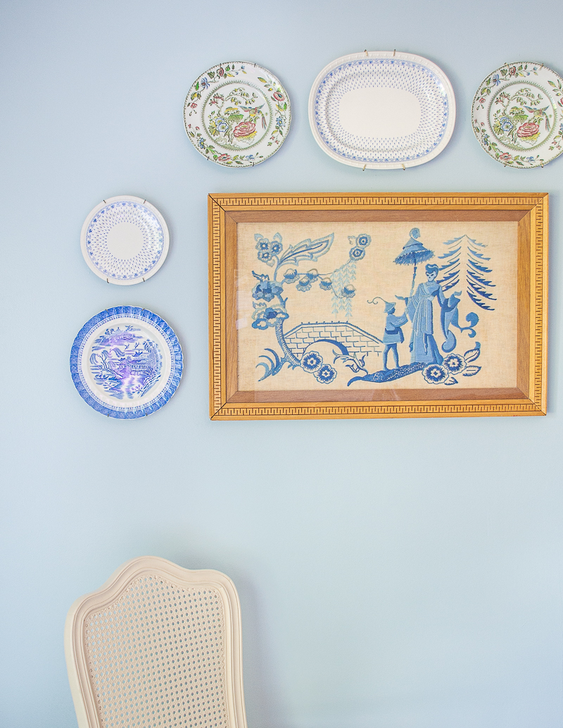 Chinoiserie gallery wall with blue and white plates and vintage embroidery