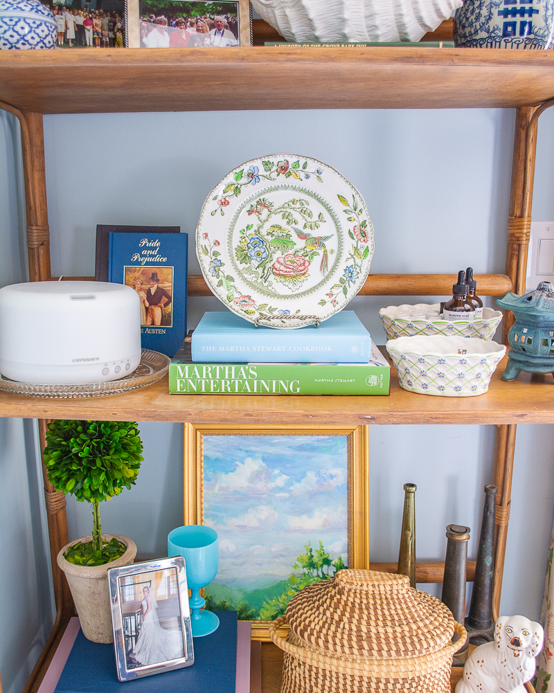 Rattan bookshelf styled with colorful paintings, baskets, family photos, and Chinoiserie accents