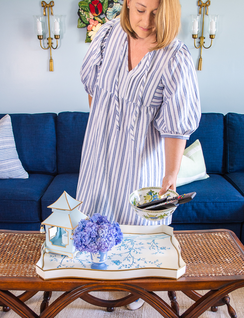 Katherine placing bowl on coffee table tray in blue and white living space