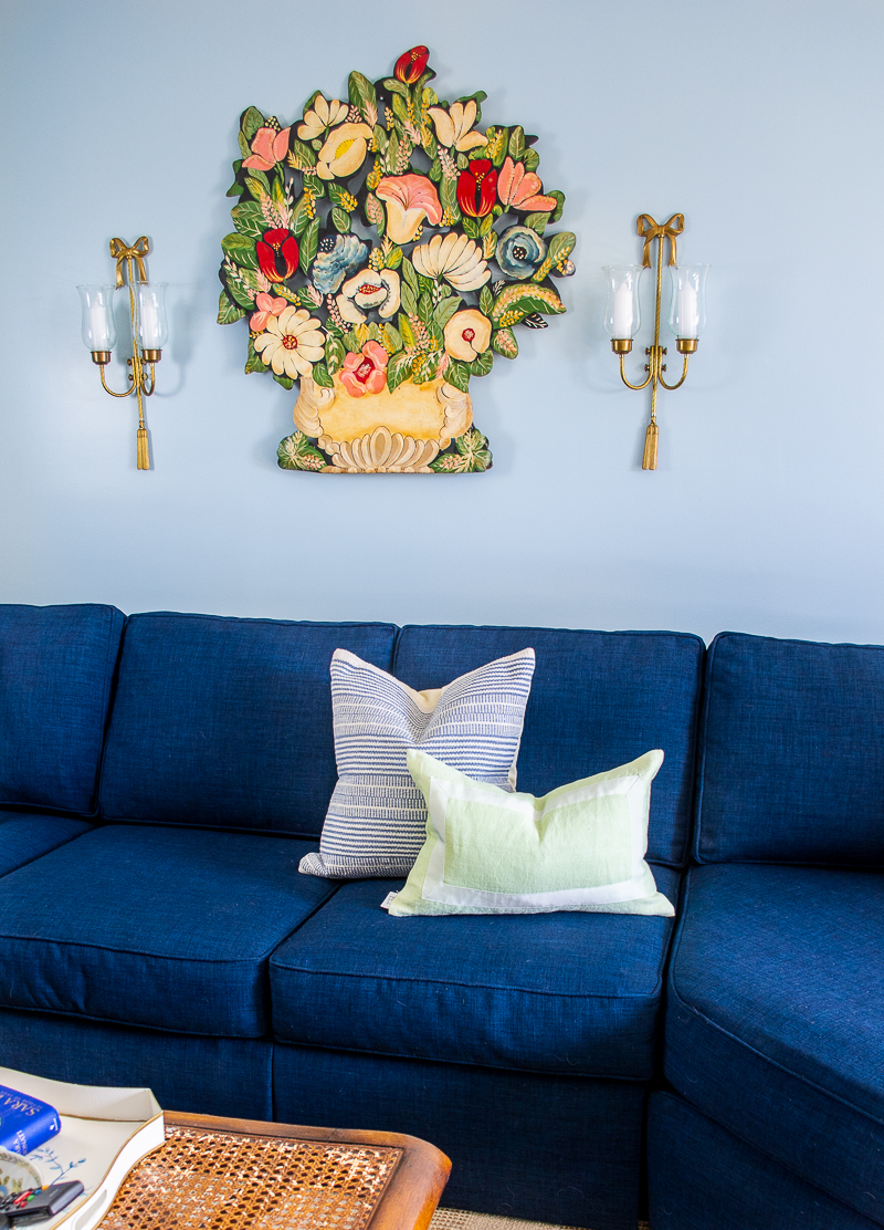 Navy section in blue and white family room with toleware art, stripe pillows, and bow sconces