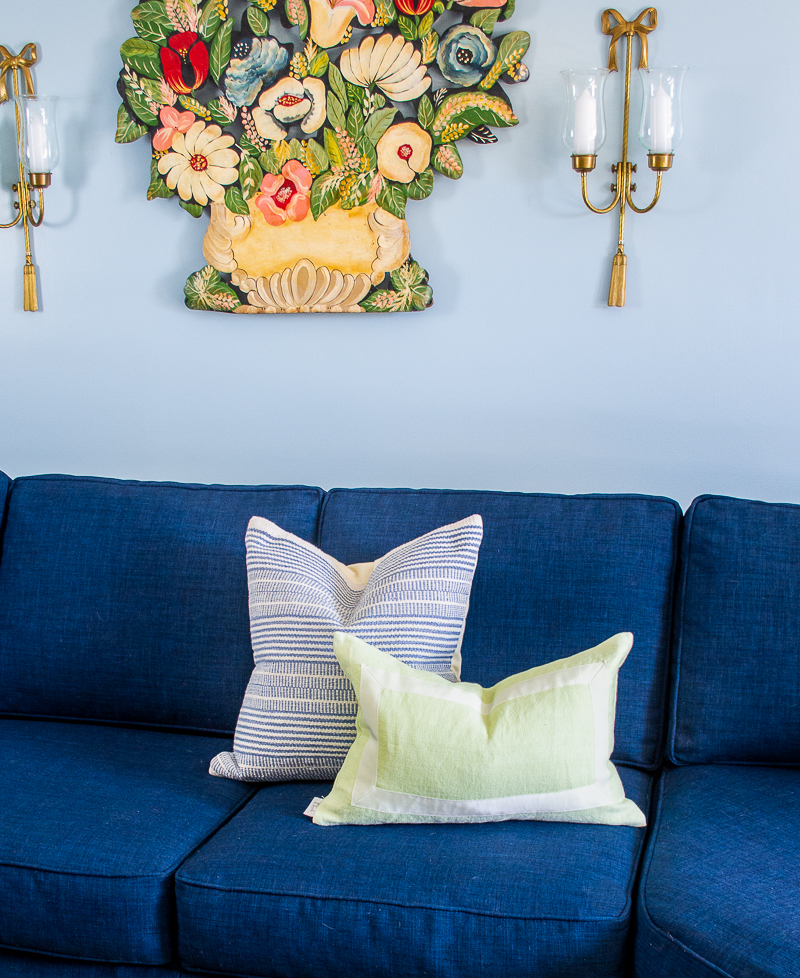 New throw pillows brighten up the navy sectional with a blue and white stripe from Birch Lane and a lime green from Lo Home