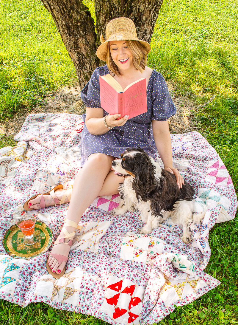 Katherine and Henry reading on a quilt under the shade of a tree