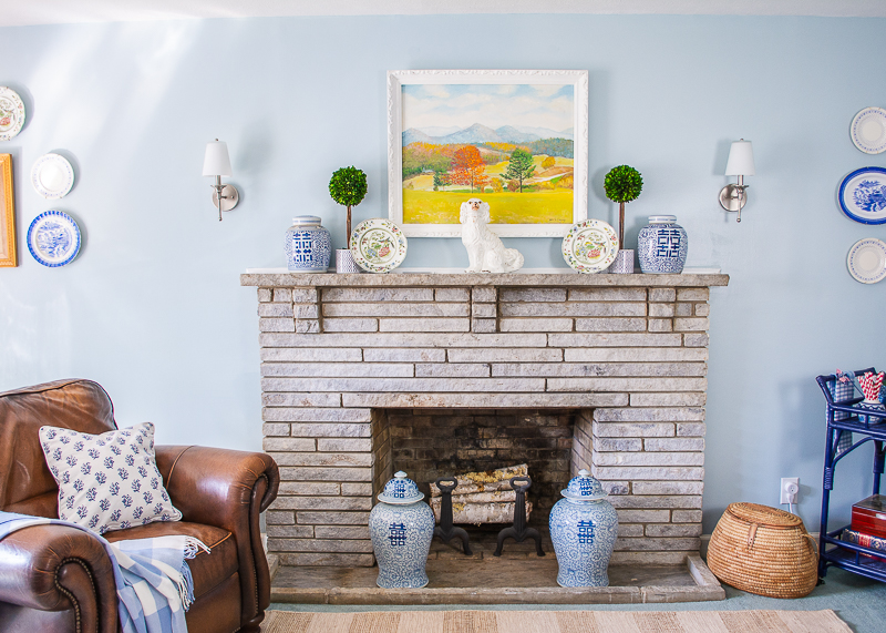 Traditional stone mantel decorated with landscape painting, blue and white ginger jars, boxwood topiary, Staffordshire spaniel