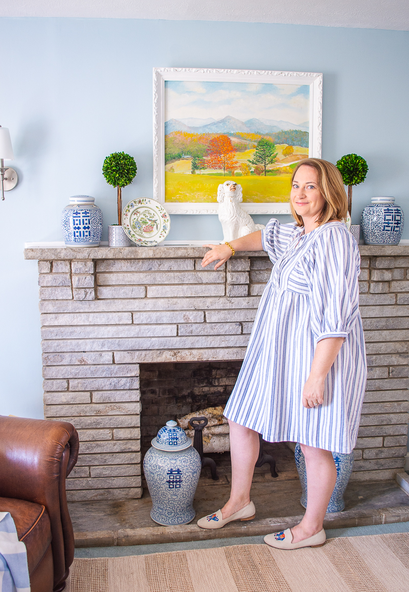 Katherine in front of re-decorated mantel in blue and white family room with blue and white double happiness ginger jars
