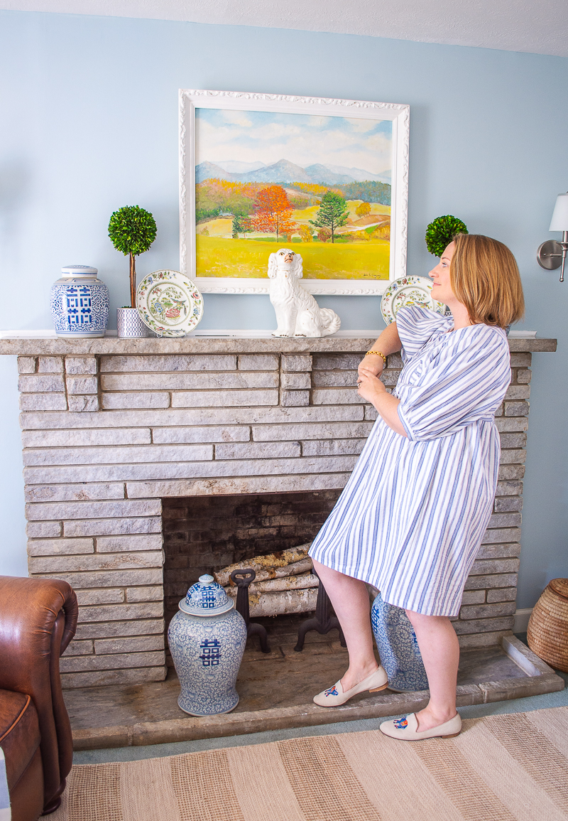 Katherine gazes up a landscape painting above mantel in re-decorated blue and white family room