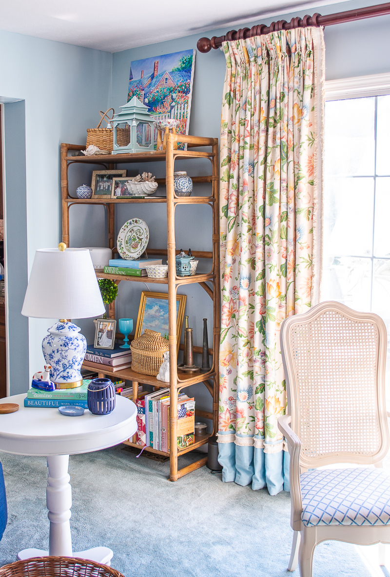 Thrifted floral curtains in vibrant blues, greens, and pinks brighten up the family room