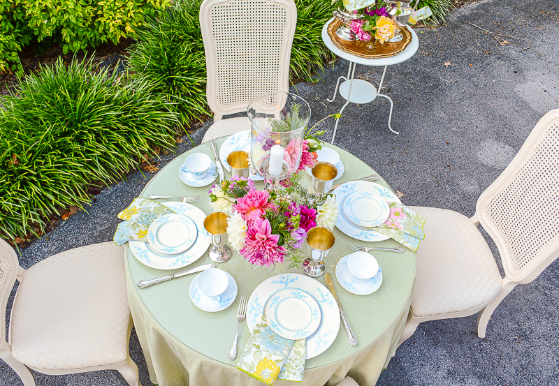 Grandmillennial summer table with pale green linen, Spode blue and white china, silver goblets, and dahlias