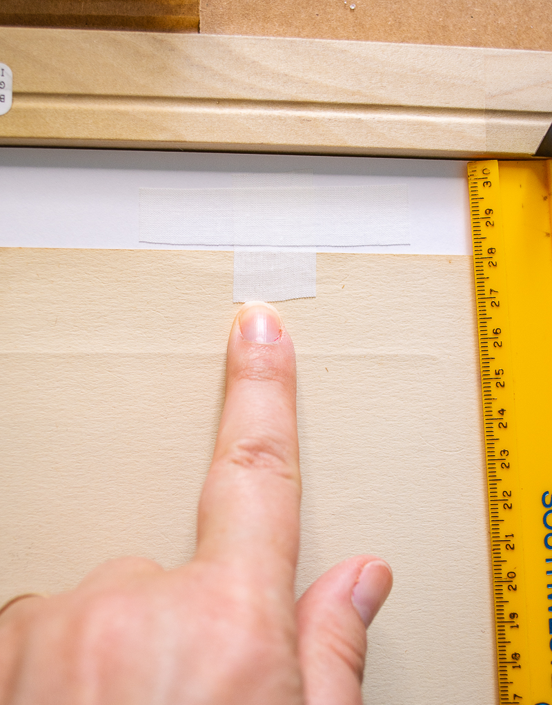 """Create """"T"""" shaped hinge with acid free tape to secure print to mat"""