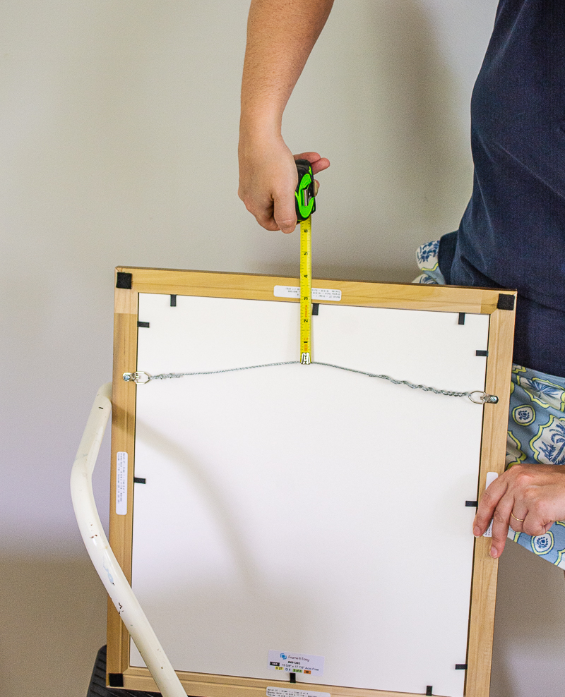 Katherine shows measurement between top of hanging wire and frame