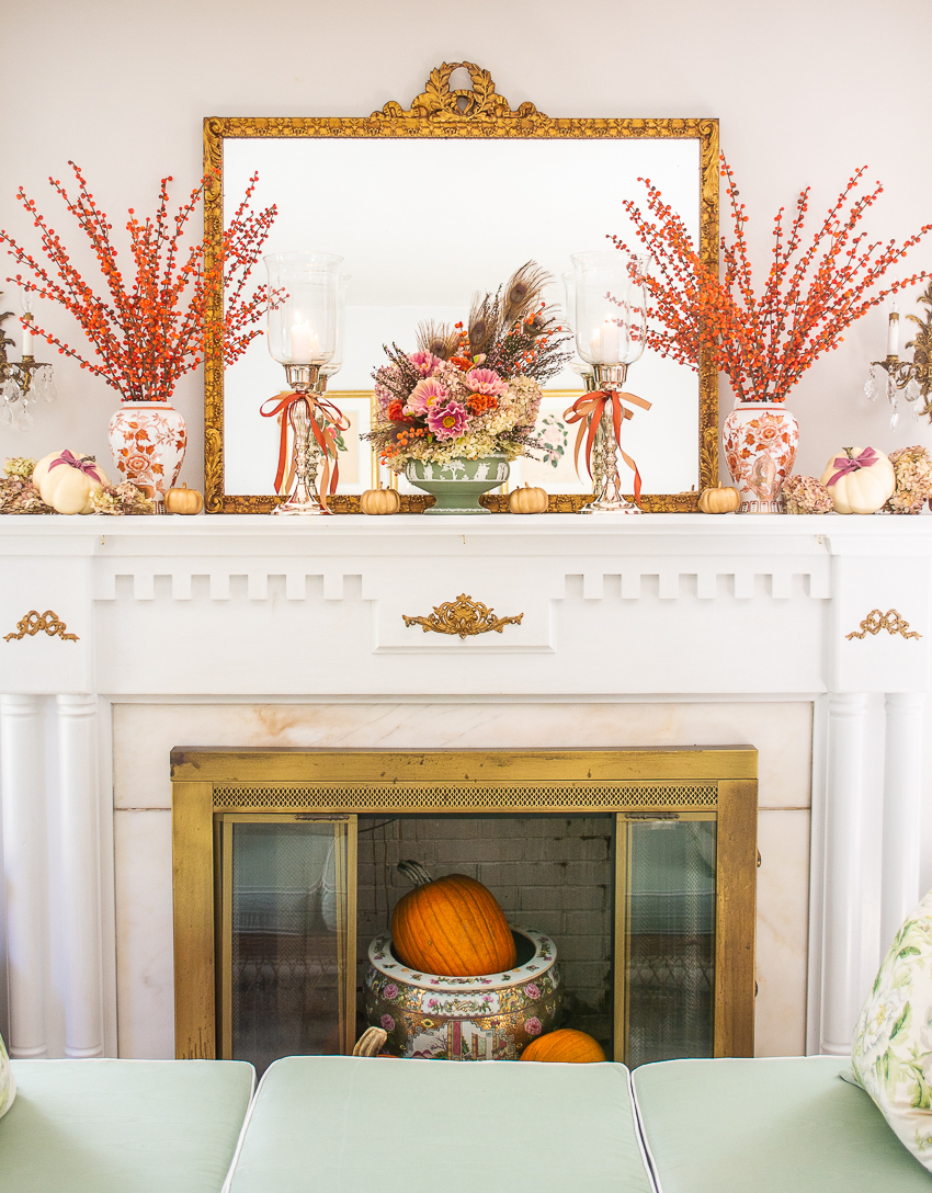 Dressing an elegant fall mantel with orange berry stems, Chinese vases, and fall florals arranged in green Wedgwood Jasperware