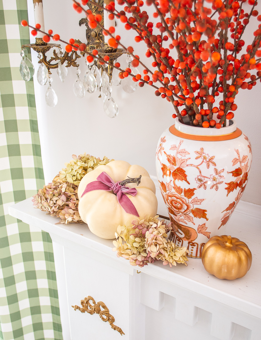 Small white pumpkin tied with pink velvet bow and nestled in preserved hydrangea