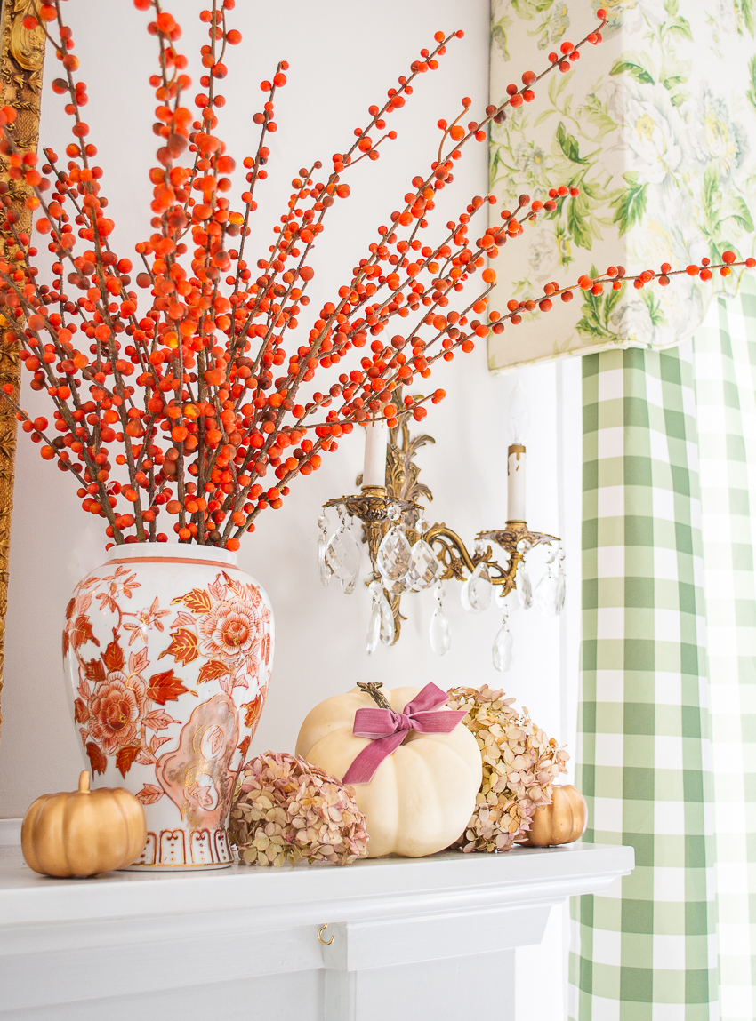 Small white pumpkin nestled in dried hydrangea blooms surrounding an orange and white Chinese vase filled with orange berry branches
