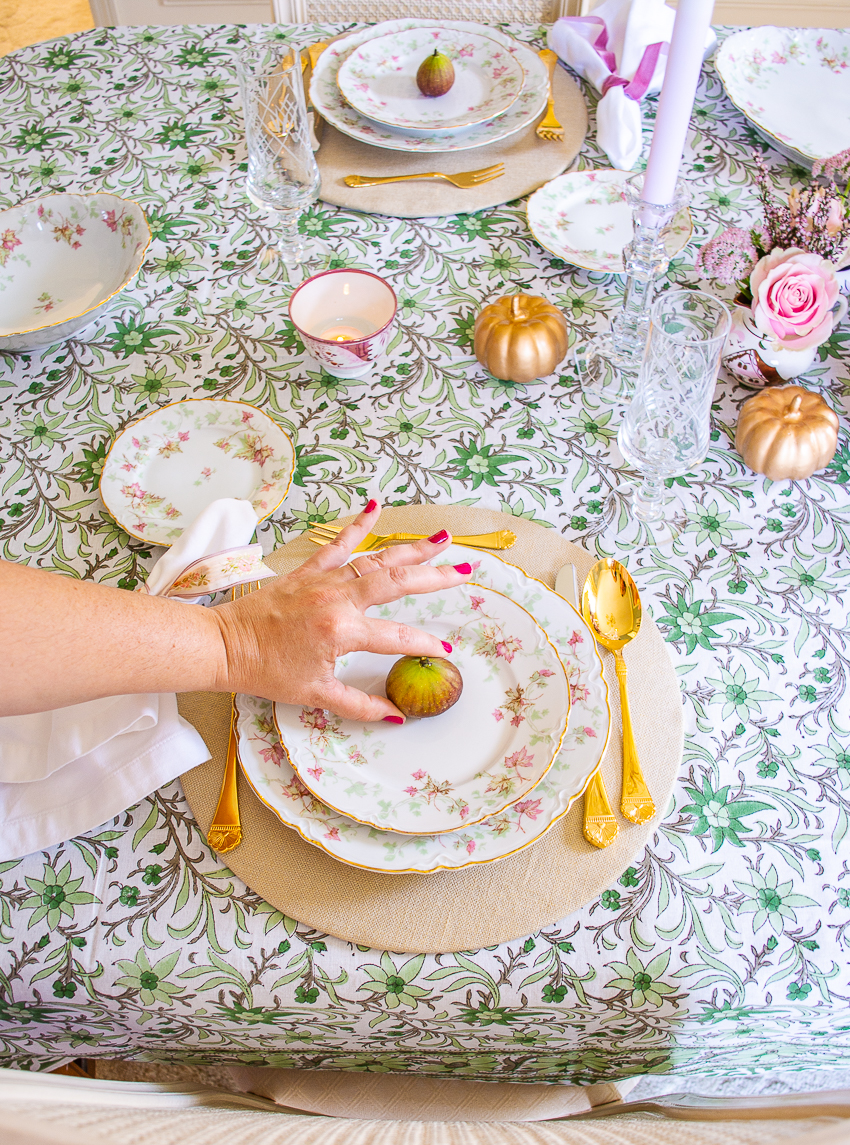 Katherine places fig on plates for autumn themed tablescape in pink and green