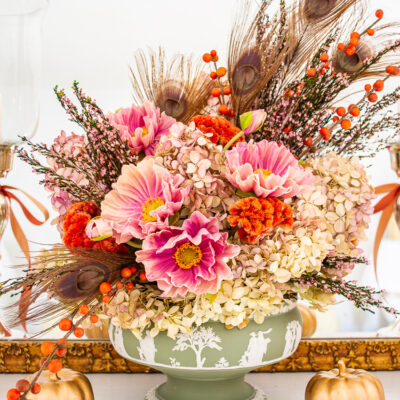Dried hydrangea, peacock feathers, purple poppies, and orange berries fill this antique Wedgwood Jasperware compote for an elegant floral arrangement for autumn