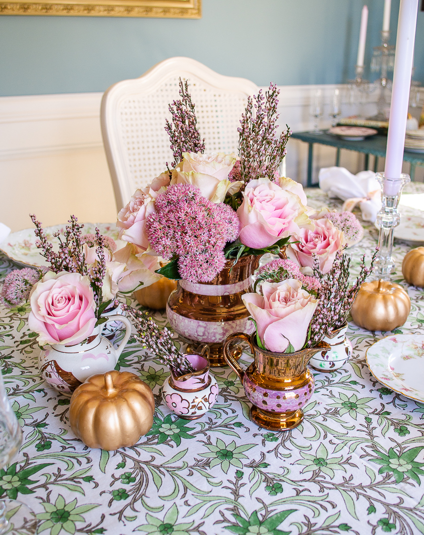 antique copper luster pitchers filled with pale pink roses, heather, and sedum decorate the center of this pink and green fall table