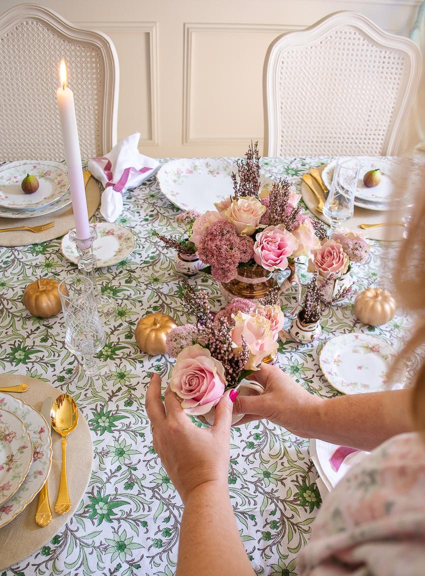 Katherine places mini pitcher flower arrangement on autumn table
