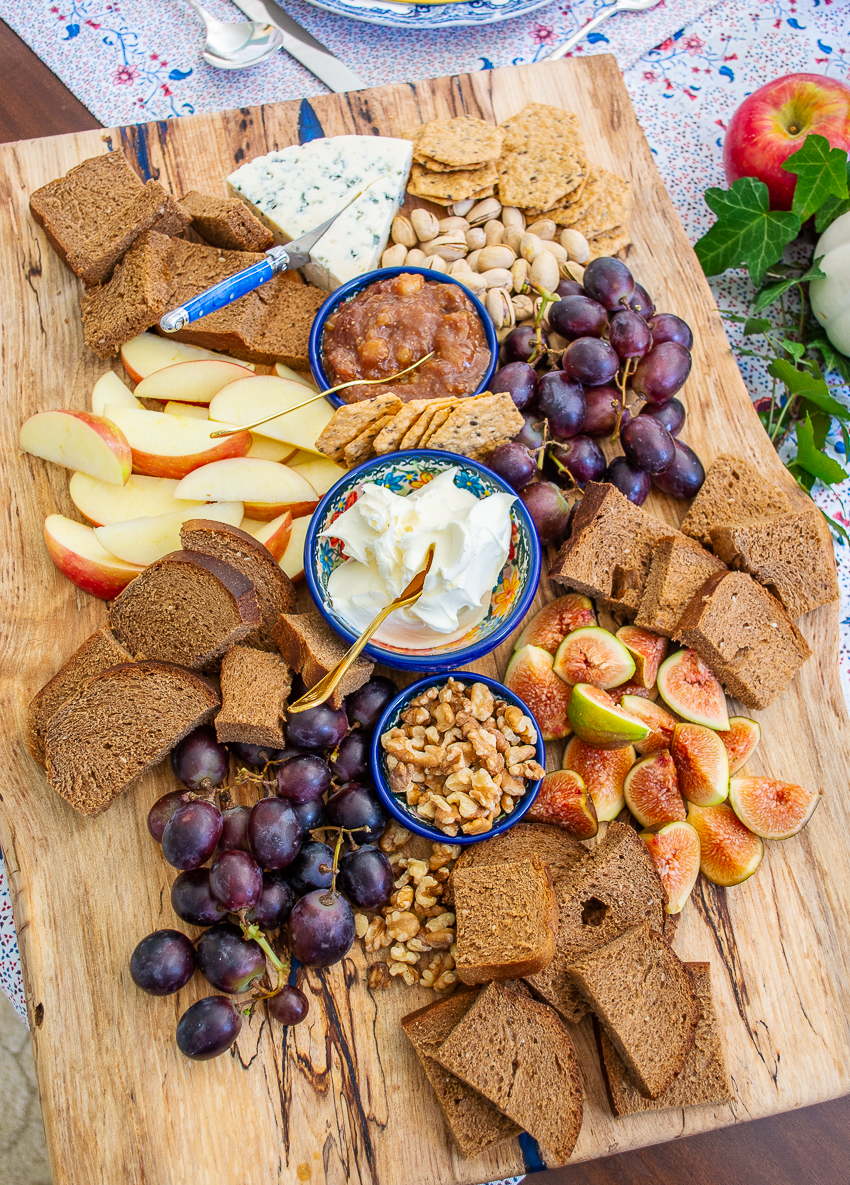 Autumn cheese board with figs, grapes, apples, and marscapone