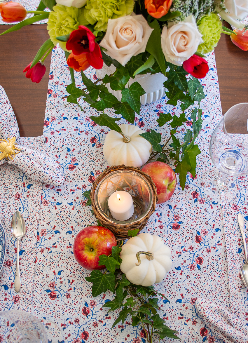 Sarah Flint burgundy floral runner with white pumpkins and red apples nestled amongst ivy vines down center of table