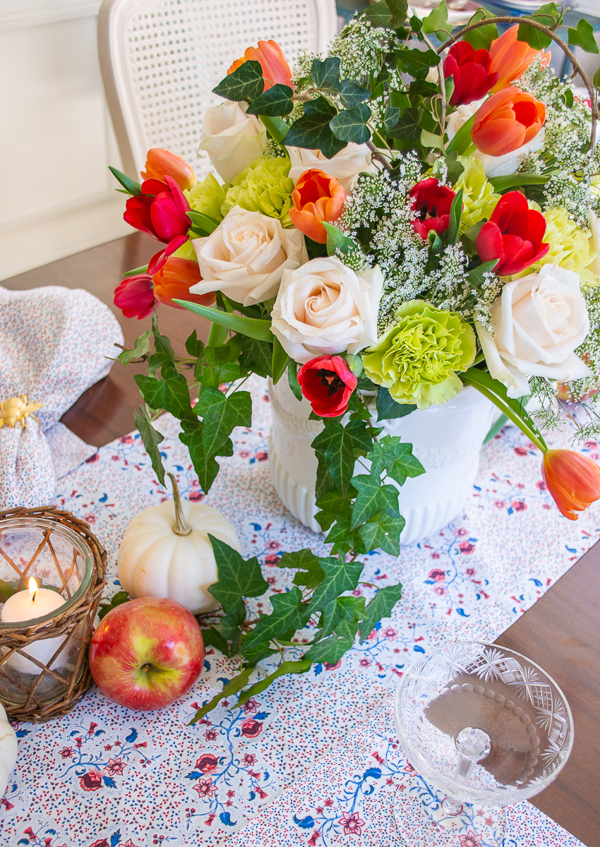 Fall floral centerpiece with white roses, orange and red tulips, lime carnations, and ivy