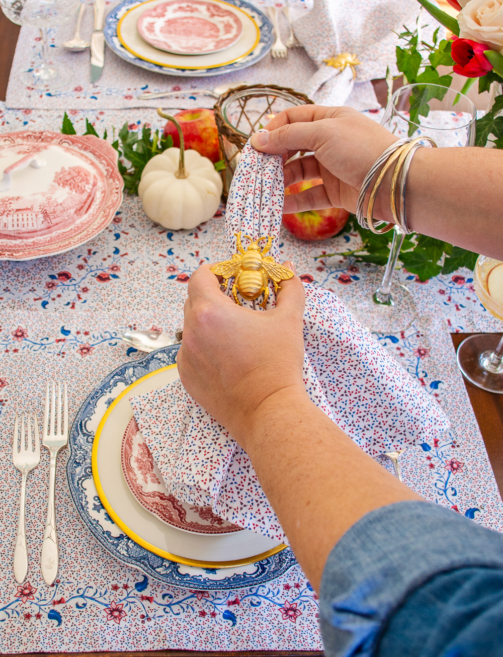 Pulling Sarah Flint burgundy floral cotton napkin through gold bee napkin ring to set fall dinner party table